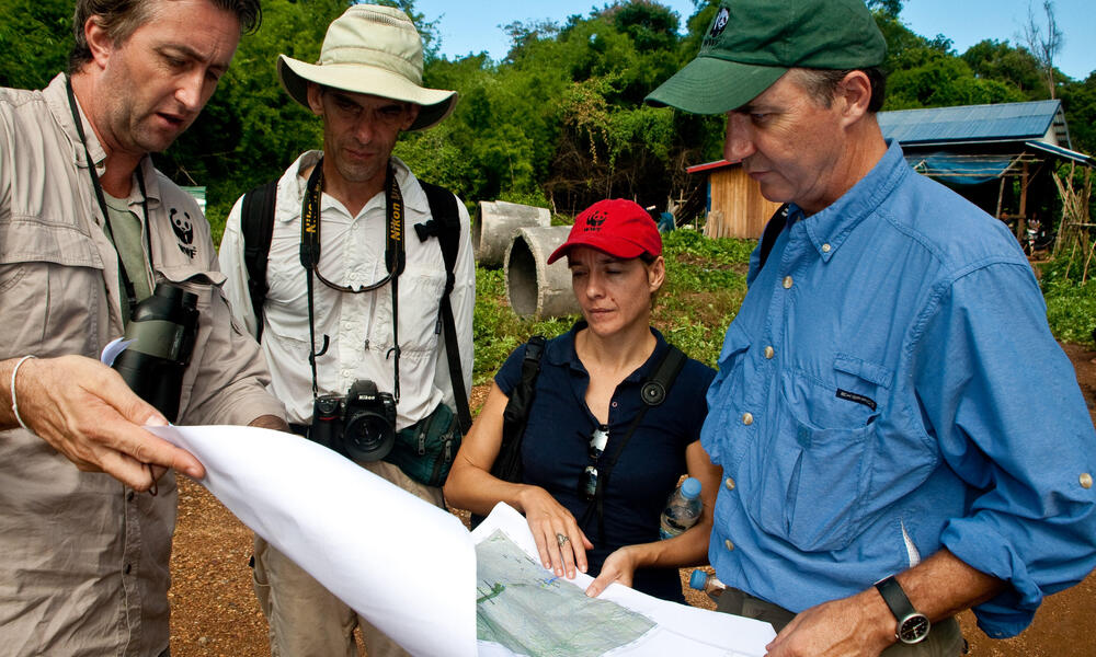 WWF staff reviewing a map of the Mekong River Basin. From left to right: Stuart Chapman, Interim Representative for WWF's Greater Mekong Program; Gordon Congdon, Freshwater Coordinator, WWF-Cambodia; Michelle Owen, Country Director, WWF-Cambodia; Carter R