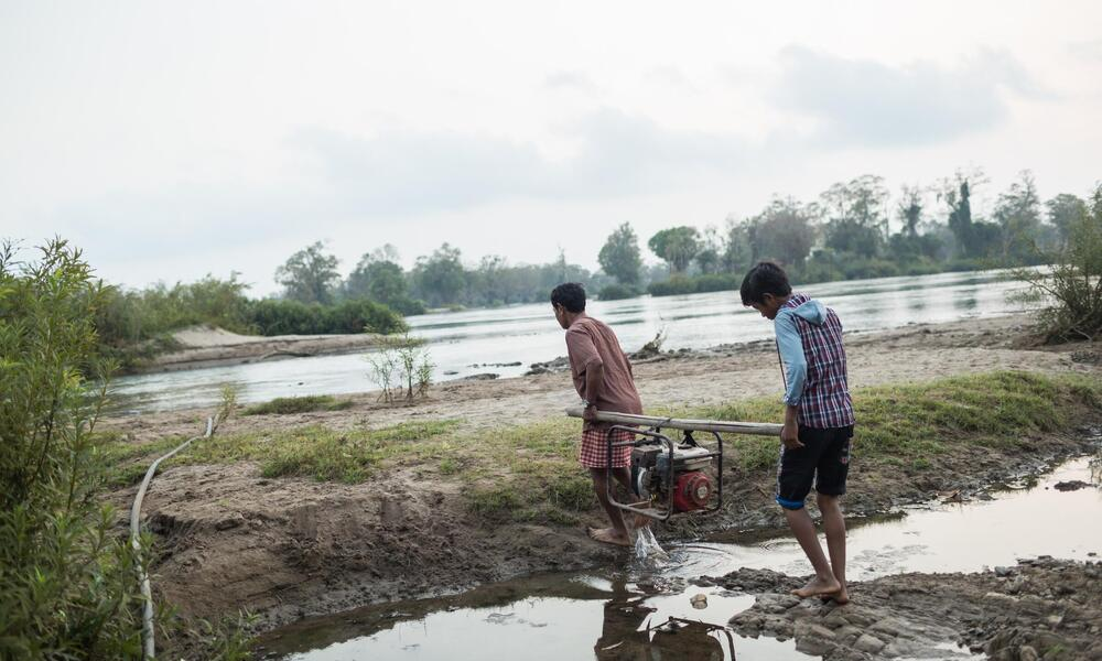 Mea Sakhorn prepares to pump water from the Mekong river.