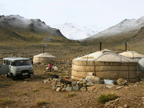 Three white covered yurt houses against a snowy mountain backdrop