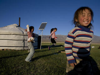 Children playing on the grass in front of their yurt home