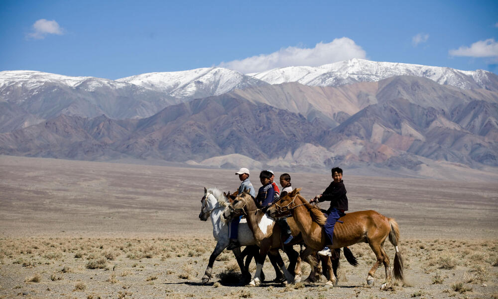 A group of children on horseback in a row in front of a large mountain range
