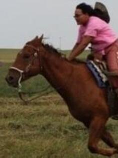 Monica Terkildsen riding a horse