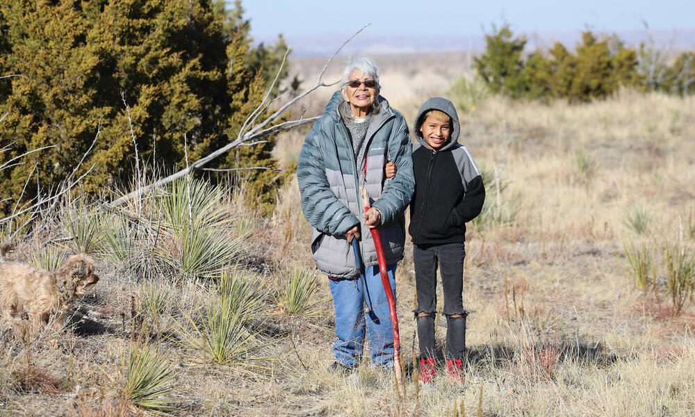 Older woman and child standing amongst scrub plants