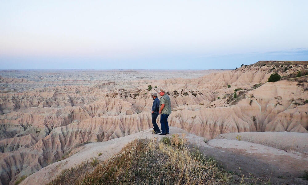 Two men standing on rock formations