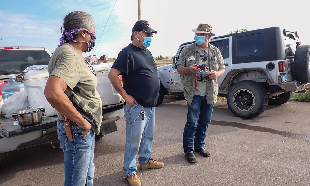 People in masks standing near trucks