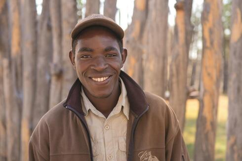 Nelson Sabata, a guide at Camp Chobe, outside his home in Katounyana.