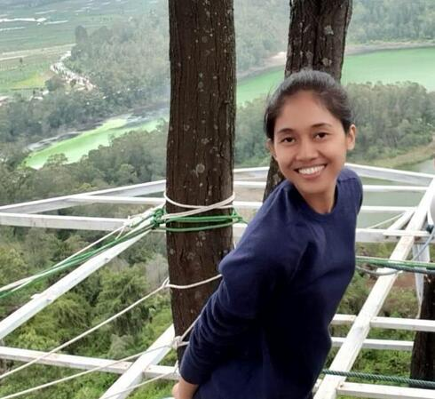 Nety Riana Sari stands beside a tree overlooking a forest and smiles at the camera