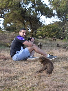 WWF Scientist Nikhil Advani sitting in field with surrounded by baboons