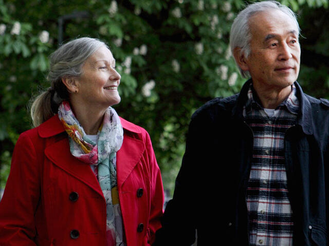 An older couple holds hands while walking through trees