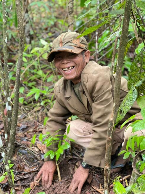 Older man in a hat crouching and smiling while planting a tree in Laos
