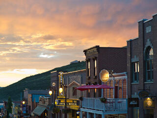 Glowing storefronts amid a pink sunset.