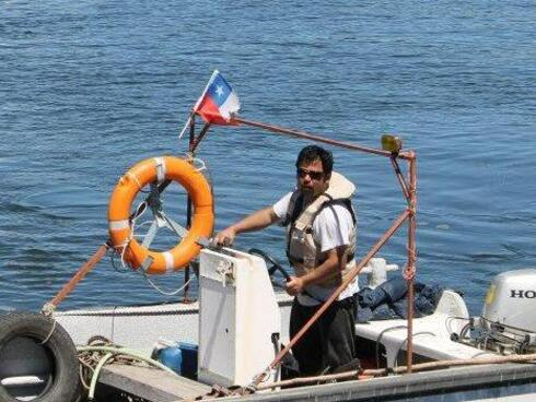 A man wearing sunglases and a life vest drives a boat across blue waters