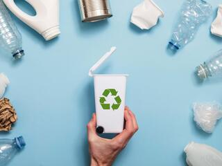 A semi circle of plastics surround a tiny recycling bin on a blue background
