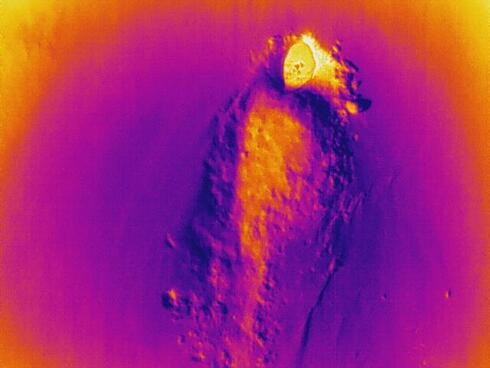 An empty polar bear den illuminated through thermal imagery on a remote-controlled flying drone.