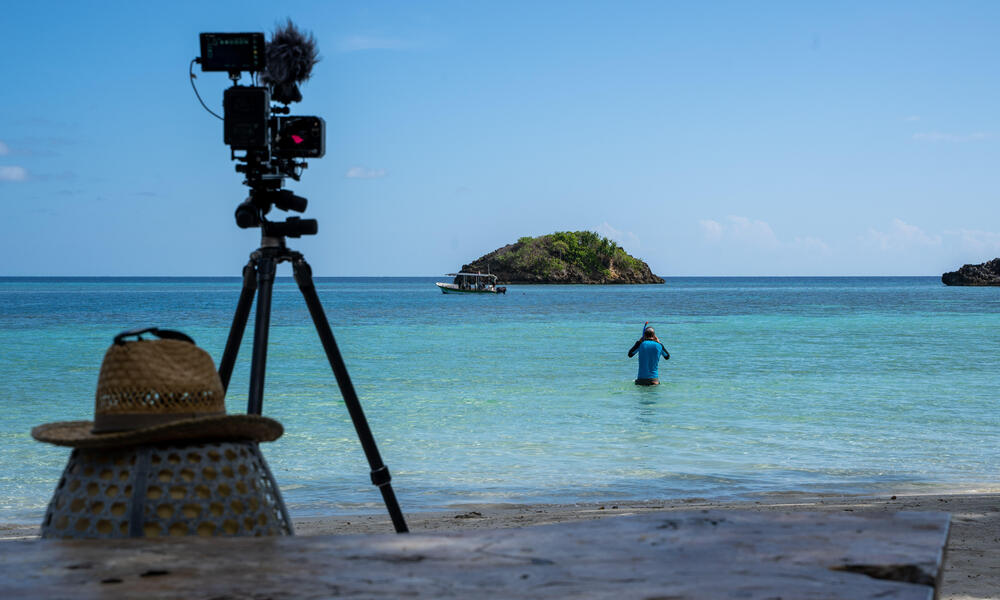 A snorkeler wades out into the calm, blue ocean at Raja Ampat. There is a camera on a tripod recording the scene in the foreground.
