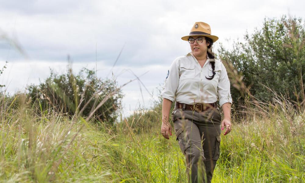 Ranger Liliana Alzogaray walks through tall grass in the Chaco on a cloudy day