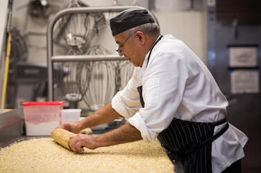 A chef rolls out dough on a counter in a hotel kitchen