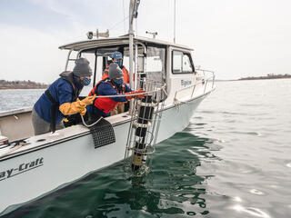 Two scientiests on a boat lower instrument into the waters of a seaweed farm off the coast of Maine