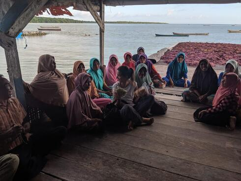 Shauna Mahajan sits in the middle of a group of women wearing colorful head wear on a dock on the water.
