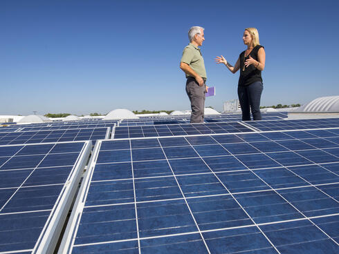 two people talk next to solar panels