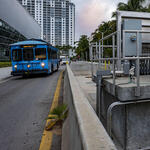 A blue bus on the South Beach Line passes a pump station