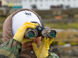 Closeup of a woman looking through binnoculars, wearing yellow gloves and a white hat, blurry background
