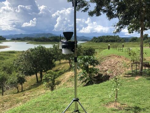 A weather station sits alongside a river on a sunny day.