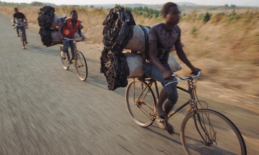 men transport charcoal by bicycle