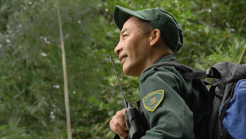 Profile portrait of a man in a green uniform with a hand radio looking off into a forest