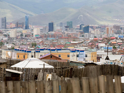 Landscape view of a city against a mountainous backdrop with a wooden fence in the foreground