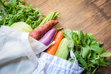 Vegetables in a tote bag on a counter