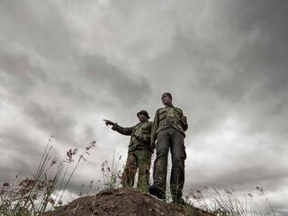 Two village game scouts stand on a rock and look over the landscape.