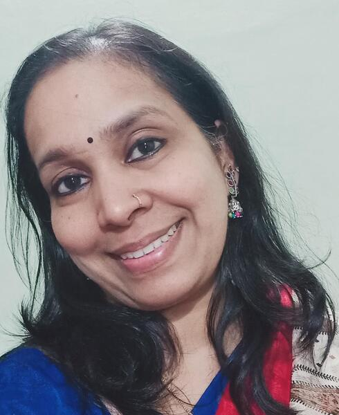 Portrait of Vineetha Aravind smiling at the camera with a white background