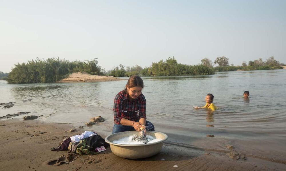 Vutra washes clothing in river