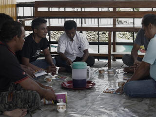 A group of men sit in a circle on a tile floor having a discussion