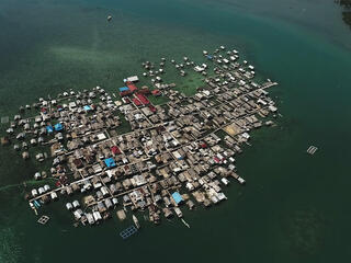 Aerial view of an island village cluster of houses built on stilts and docks out in the water