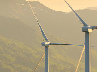 Two wind turbines on a mountain in Alaska with a setting sun and mountains in the background