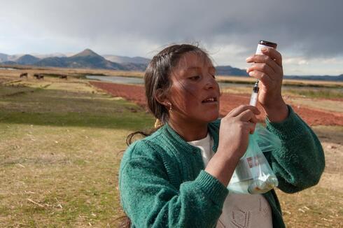 Woman filling syringe with medicine