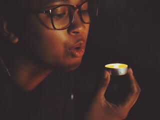 A woman blows out a candle