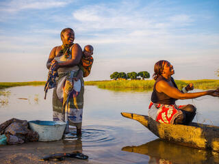 Two women and a baby on a river bank, one washing clothes and the other casting a net while all smile