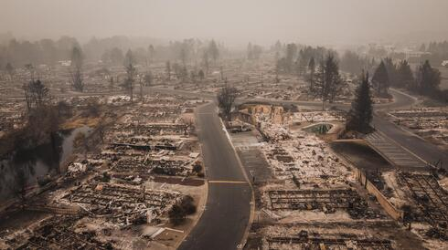 Aerial view of a neighborhood scorched by wildfire with only foundations left of houses