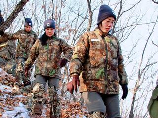 An all-female team of rangers treks through a snowy forest in China looking for clues of big cat whereabouts
