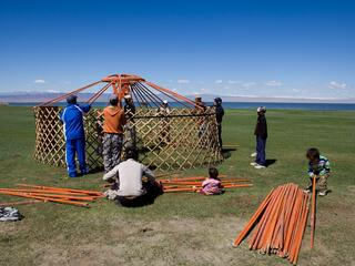 A group of people build a yurt with lattice wood walls on a grassy landscape