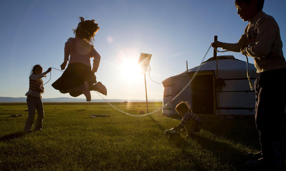 Three children jumping rope on the grass in the sunset