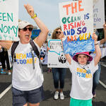 """people hold up signs that read """"green economy"""" and """"the ocean is rising and so are we"""""""