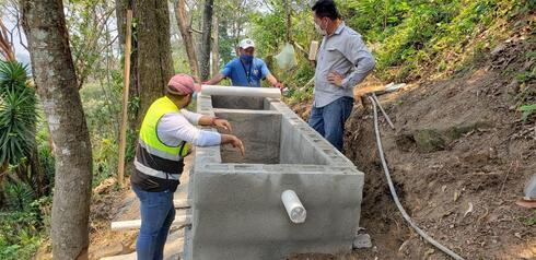 Three men stand around a cement structure in the forest while building a new water system