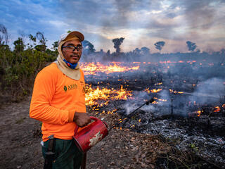 Man in front of burning ground