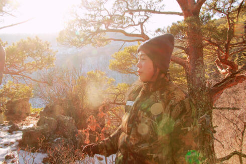 A female ranger prepares to begin her day, standing against a forest backdrop as the sun rises