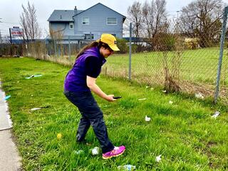 Woman in a yellow hat standing in the grass next to a chain link fence taking photos with a cell phone of trash in the grass