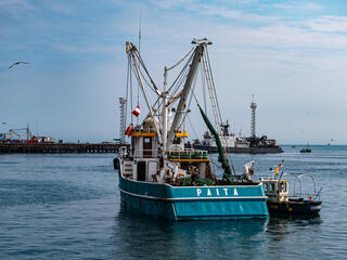The rear view of a large blue industrial fishing boat on the water